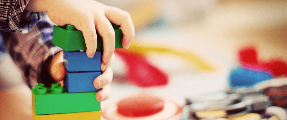 A child's hands play with Lego blocks