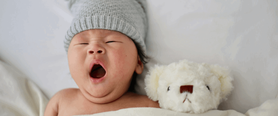 Infant in bed wearing a gray skull cap beanie next to small teddy bear yawning