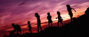 A row children in silhouette background red setting sun sky