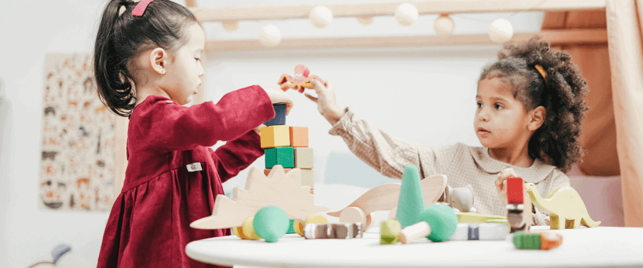 Two girls playing seated at a table playing with blocks