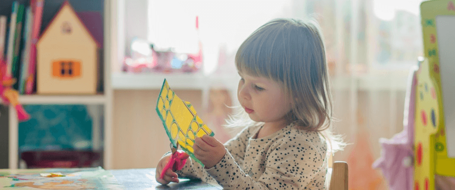 Young girl cutting up paper sitting at a small desk