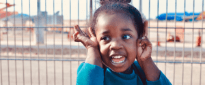 Close up image of a young girl with her hands on her face in a playground
